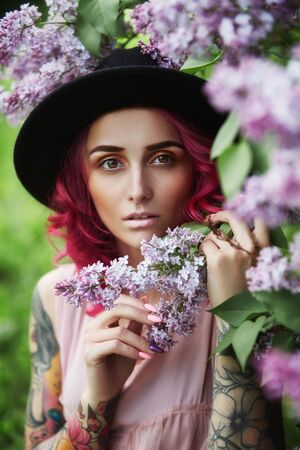Fashion girl with red hair and big hat vocation, spring portrait in lilac colors in summer. Beautiful red pink dress, tattoos on the body of a woman. Bright make-up, professional hair coloring