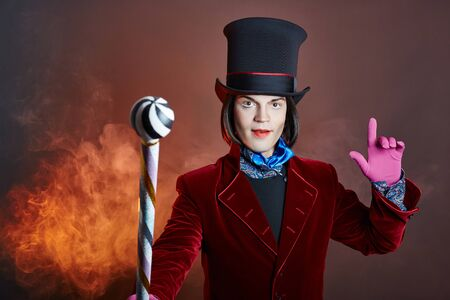 Fabulous circus man in a hat and a red suit posing in the smoke on a colored dark background. A clown at a party, man gentleman from a fairy tale. Wizard with a cane, ice cream and chocolate in hands
