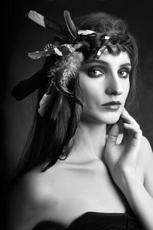 Mujer india con plumas en el pelo, retrato de belleza de niña india americana sobre fondo oscuro en humo. Hermoso rostro con piel limpia, maquillaje en contraste. Foto de archivo