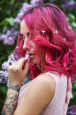 Fashion girl with red hair and big hat vocation, spring portrait in lilac colors in summer. Beautiful red pink dress, tattoos on the body of a woman. Bright make-up, professional hair coloring Imagens - 128237558
