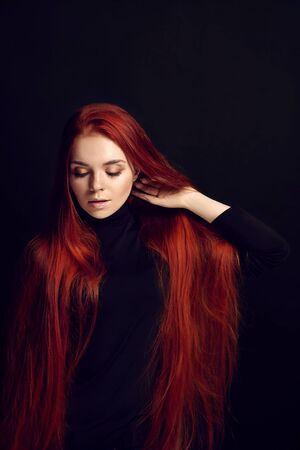 Sexy beautiful redhead girl with long hair. Perfect woman portrait on black background. Gorgeous hair and deep eyes. Natural beauty, clean skin, facial care and hair. Strong and thick hair