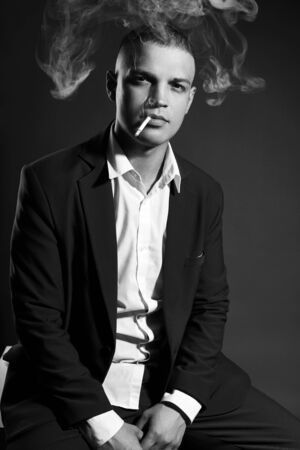 Contrast portrait of a Smoking man businessman in an expensive business suit on a dark background. Successful emotional Manager businessman posing gestures hands and Smoking cigarette on a black Reklamní fotografie