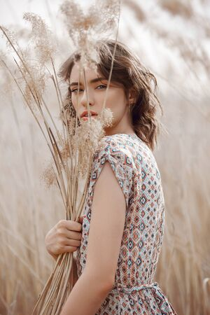 Beautiful girl in a field with tall grass in autumn. Art portrait of a woman, romantic mysterious look. Fashion natural cosmetics and makeup, beautiful hair