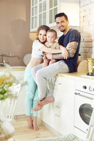 Married couple and their little baby baby in her arms. Young family at home in the morning on a day off. Joyful and happy faces hugging and having fun