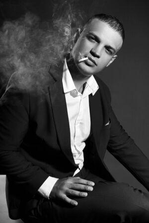 Ritratto a contrasto di un uomo d'affari fumatori in un vestito costoso su uno sfondo scuro. Imprenditore di successo manager emotivo in posa gesti mani e fumo di sigaretta su un nero