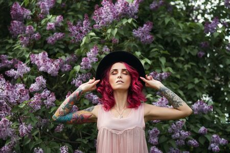 Spring beauty portrait of a beautiful girl with red hair in the branches of a blooming lilac. Lilac flowers in the hands and hair of a woman. Natural makeup