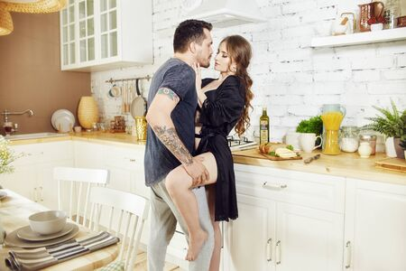 Couple in love in the kitchen in the morning hugs and prepares Breakfast. Happy family life. Joy and smiles on the face of men and women. Love and relationships