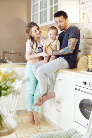 Couple and their little baby baby in arms. Young family at home in the morning on a day off sitting in the kitchen. Joyful and happy faces hugging and having fun Reklamní fotografie