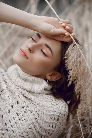Autumn beauty portrait of a beautiful girl in a field in the grass rays of the sunset. Lifestyle woman with natural makeup on nature. Romantic autumn mood, long tall grass in the meadow Reklamní fotografie
