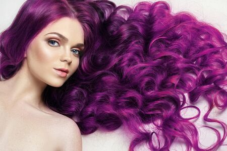 Creative bright coloring of a womans hair, careful care of the hair roots. Bright dye for coloring, long strong hair. Natural cosmetics, natural beauty. Girl with red, redhead, purple hair