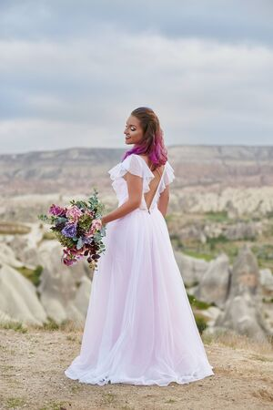 Woman with beautiful bouquet of flowers in hands stands on mountain in rays of dawn sunset. Beautiful white long dress on the girl body. Perfect bride with pink hair. Turkey, Cappadocia