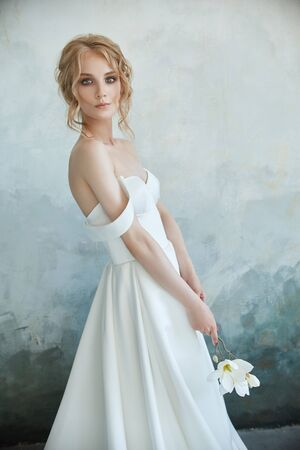 Girl in a chic long dress sitting on the floor. White wedding dress on the brides body. Beautiful light dress with a long hem, a portrait of a fragile delicate girl before the wedding ceremony