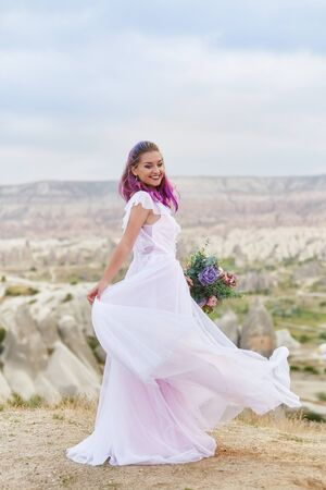 Beautiful white long dress on the girl body. Perfect bride with pink hair dance. Woman with a beautiful bouquet of flowers in her hands dance on the mountain in the rays of the dawn sunset