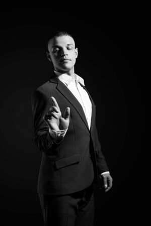 Contrast portrait of a man businessman in an expensive business suit on a dark background. Successful emotional Manager businessman posing gestures with his hands on black