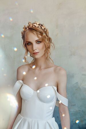 Beautiful slender blonde in the evening sun in a long white dress. Portrait of a woman with a flower in her hand. Perfect hairstyle and cosmetics of the bride, a new collection of wedding dresses