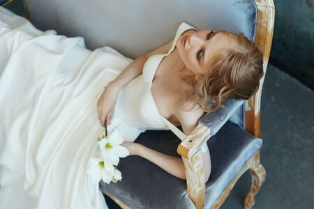 Beautiful slender blonde girl sitting on the sofa in a long white dress. Portrait of a woman with a flower in hand. Perfect hairstyle and cosmetics of the bride, new collection of wedding dresses Reklamní fotografie