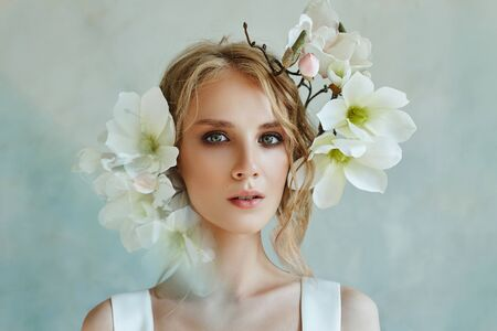 Perfect bride with jewels, a portrait of a girl in a long white dress. Beautiful hair and clean delicate skin. Wedding hairstyle blonde woman. Girl with a white flower in her hands Stok Fotoğraf - 130037524