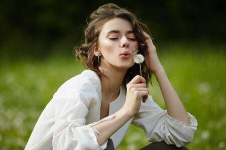 Spring portrait of a girl sitting in a field on the grass among dandelion flowers. Cheerful girl enjoys Sunny spring weather. Natural beauty of a woman, natural cosmetics Stockfoto