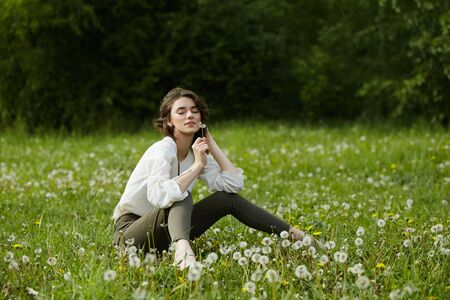 Portrait of a girl sitting in a field on the spring grass among dandelion flowers. Cheerful girl enjoys Sunny spring weather. Natural beauty of a woman, natural cosmetics