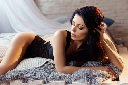 Femme brune sexy en lingerie noire à la maison sur le lit. Silhouette parfaite, beau corps sur la fille. Peau propre et lisse et cheveux longs et forts. La fille à la lumière de la lampe jaune