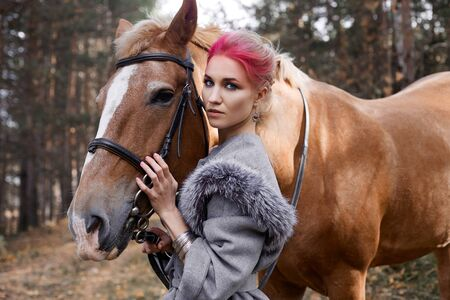Woman on a horse in the fall. Creative bright pink makeup on the girl face, hair coloring. Portrait of a girl with a horse. Horseback riding in the autumn forest. Autumn clothes Stock fotó