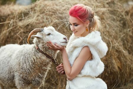 Woman bright red makeup on face hugs horned RAM. Creative hot pink makeup on girl face, hair coloring. Portrait of a girl with a sheep. Walk in the autumn forest. Autumn woolen clothes Zdjęcie Seryjne