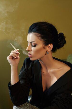 Schöne Mode Nackte selbstbewusste Frau mit schwarzem Haar Rauchen einer Zigarette auf einem Stuhl in einer schwarzen Jacke. Perfekter Körper glatte, saubere Haut. Stilvolles Portrait einer Frau