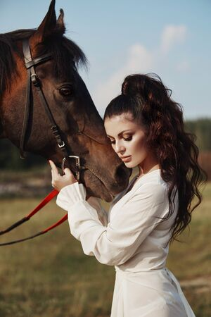 Girl in a long dress stands near a horse, a beautiful woman strokes a horse and holds the bridle in a field in autumn. Country life and fashion, noble steed