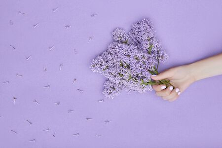 Beauty Hand of a woman with blue flowers lies on table, blue paper background. Natural cosmetics product and hand care, moisturizing and wrinkle reduction, skincare Stockfoto