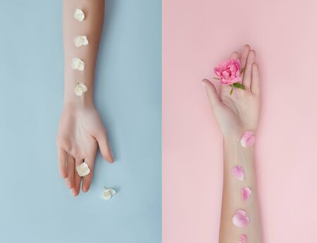 Hand with pink flowers and petals lying on a paper background. Cosmetics for hand skin care. Natural petal cosmetics, essential oils, anti-wrinkle and anti-aging hand care Zdjęcie Seryjne - 133112041