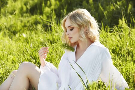 Girl in a long white dress sits on the grass in a field. Blonde woman in the sun in a light dress. Girl resting and dreaming, perfect summer makeup on her face