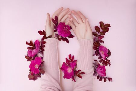 Hand with pink flowers and petals lying on a paper background. Cosmetics for hand skin care. Natural petal cosmetics, essential oils, anti-wrinkle and anti-aging hand care Zdjęcie Seryjne - 133110673