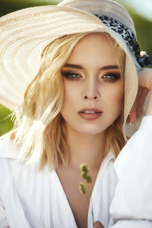 Girl in a big hat and a long white dress is sitting in the grass in a field. Blonde woman in the sun in a light dress. Girl resting and dreaming, perfect summer makeup on her face Stockfoto