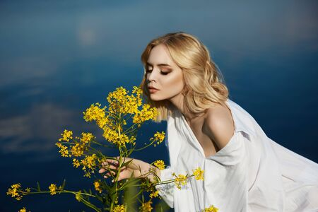 Girl in a long white dress with a flower in her hand stands near the lake. Blonde woman in the sun in a light dress. Girl resting and dreaming, perfect summer makeup on her face