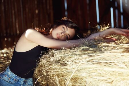 Girl resting in the village near the hay, portrait of a woman in the sun, rustic style. Portrait of a sexy brunette in the hayloft. Perfect makeup, natural cosmetics Stockfoto