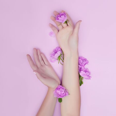 Hand with pink flowers and petals lying on a paper background. Cosmetics for hand skin care. Natural petal cosmetics, essential oils, anti-wrinkle and anti-aging hand care Zdjęcie Seryjne - 133111028