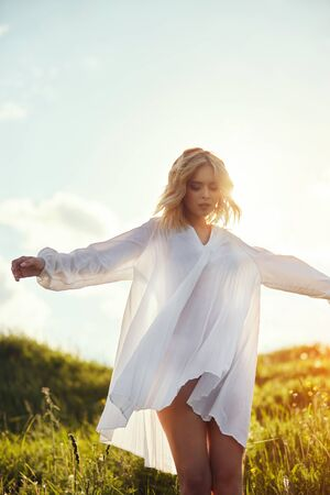 Girl in a long white dress dancing in the field. Blonde woman in the sun in a light dress. Girl resting and dreaming, perfect summer makeup on her face