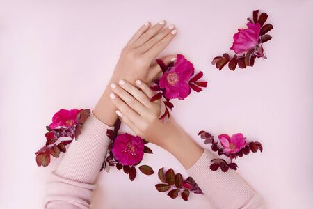 Hand with pink flowers and petals lying on a paper background. Cosmetics for hand skin care. Natural petal cosmetics, essential oils, anti-wrinkle and anti-aging hand care Zdjęcie Seryjne - 133111230