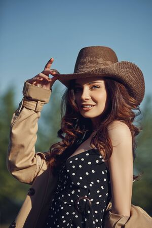 Girl in a cowboy hat resting in the village near the stables, portrait of a woman in the sun, rustic style. Portrait of a sexy brunette in nature. Perfect makeup, natural cosmetics