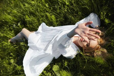 Girl in a long white dress lies on the grass in a field. Blonde woman in the sun in a light dress. Girl resting and dreaming, perfect summer makeup on her face
