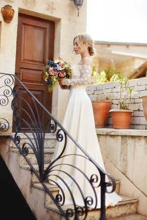 Girl with a bouquet of flowers in her hands is waiting for her beloved man near the house. A perfect hairstyle and beautiful long dress, curly hair. Love story