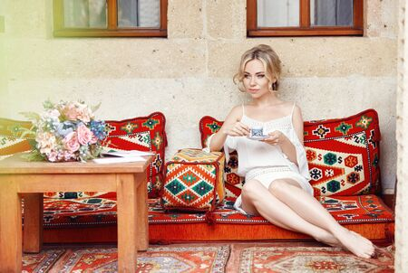 Morning girl drinking coffee resting sitting on a Turkish sofa. Woman dreaming, beautiful blonde hairstyle, hot tea in a Cup in her hands