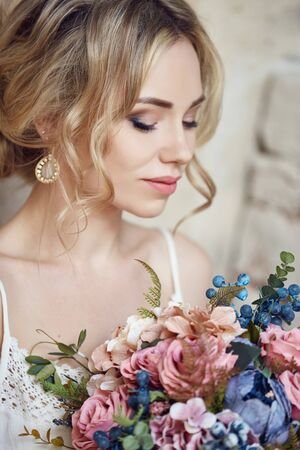 Girl with a bouquet of flowers in her hands is waiting for her beloved man near the house. Perfect hairstyle, curly hair. Love story