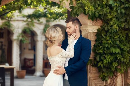 Love story of a woman and a man. Loving couple embraces, a beautiful Oriental couple. A man in a jacket and a girl in a long luxurious light dress