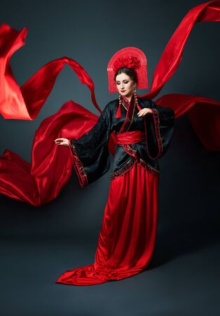 Frau ist in roter chinesischer japanischer Volkskleidung gekleidet. Fliegender Stoff, schöner Regenschirm und Fächer im japanischen chinesischen Stil, lange Ohrringe in den Ohren. Mädchen posiert auf dunklem Hintergrund Standard-Bild