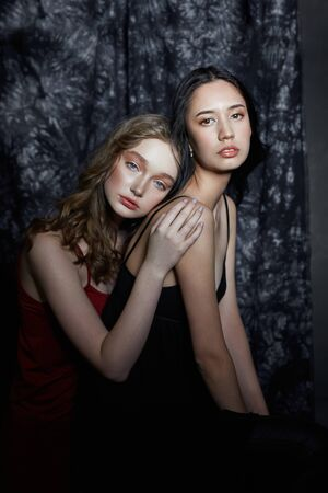 Beauty spring portrait of two girls on a dark background. Women hug and pose. Beautiful makeup and clean smooth skin, good manicure Standard-Bild - 139999251