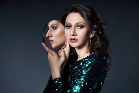 美しいイブニングメイクと彼女の手に鏡を持つ女性の美しさの肖像画、スパンコールと光沢のあるイブニングドレスを着たブルネットの女の子。顔のための自然な化粧品