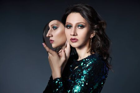 Piękno portret kobiety z pięknym makijażem wieczorowym i lustrem w dłoniach, brunetka dziewczyna w błyszczącej sukni wieczorowej z cekinami. Kosmetyki naturalne do twarzy