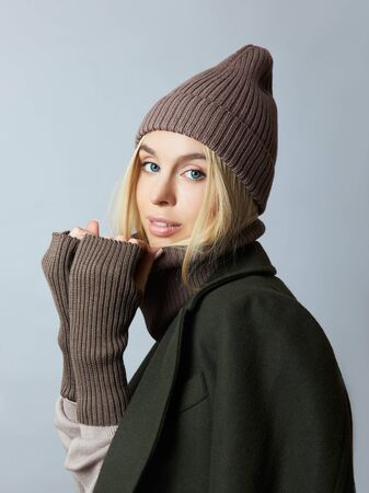 Woman in coat, spring clothes, a Snood scarf, a hat and gloves. The girl is blonde with blue eyes. Warm clothing for cold spring weather