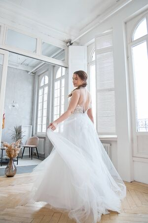 Brown-haired girl in a beautiful white wedding dress. A woman bride is waiting for the groom before the wedding